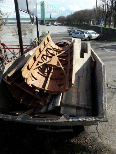Container mit Boots-Teilen, Holzresten und kaputten Biertischen